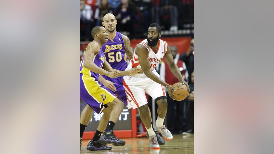 In this Jan. 8, 2014 photo, Houston Rockets' James Harden, right, is double-teamed by Los Angeles Lakers Wesley Johnson, left, and Robert Sacre (50)  in the second half of an NBA basketball game in Houston. Harden is heating up for the Houston Rockets. He's put foot and ankle problems behind him and has scored 113 points combined in the last three games.   (AP Photo/Pat Sullivan)