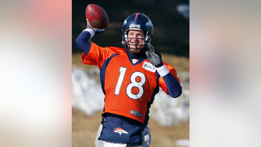 Denver Broncos quarterback Peyton Manning (18) tosses a football during practice for the football team's NFL playoff game against the San Diego Chargers at the Broncos training facility in Englewood, Colo., on Thursday, Jan. 9, 2014. (AP Photo/Ed Andrieski)
