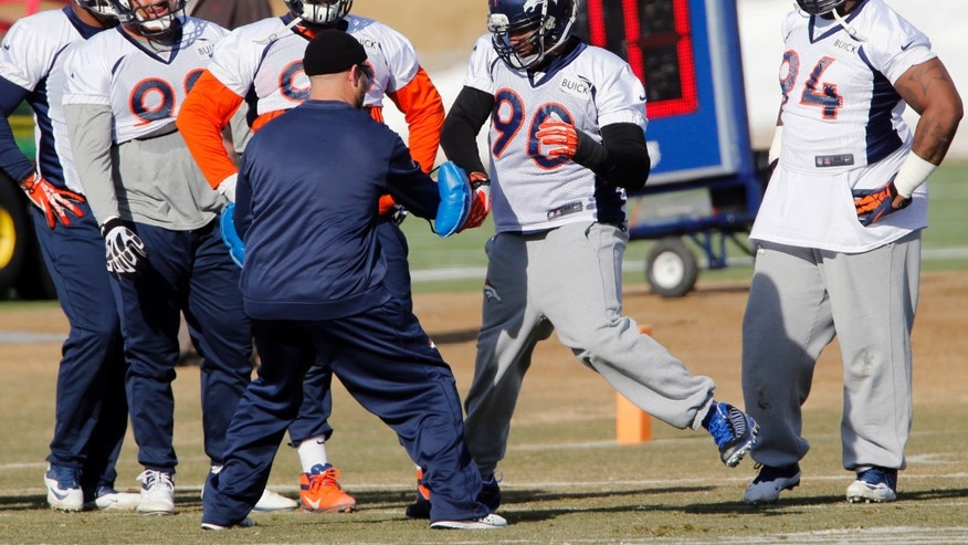 Denver Broncos defensive end Shaun Phillips (90) works on drills as other defensive linemen look on during practice for the football team's NFL playoff game against the San Diego Chargers at the Broncos training facility in Englewood, Colo., on Thursday, Jan. 9, 2014. (AP Photo/Ed Andrieski)