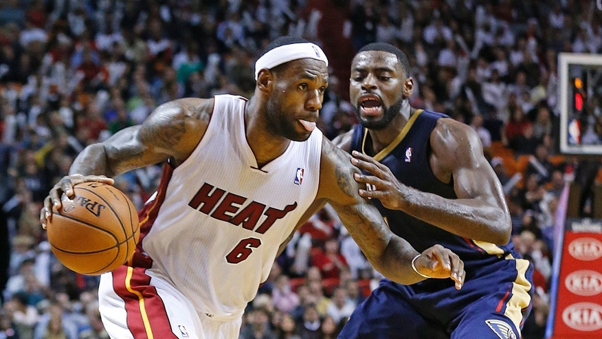 Miami Heat's LeBron James (6) drives to the basket against New Orleans Pelicans' Tyreke Evans (1) during the second half of an NBA basketball game in Miami, Tuesday, Jan 7, 2014. The Heat defeated the Pelicans 107-88. (AP Photo/Joel Auerbach)