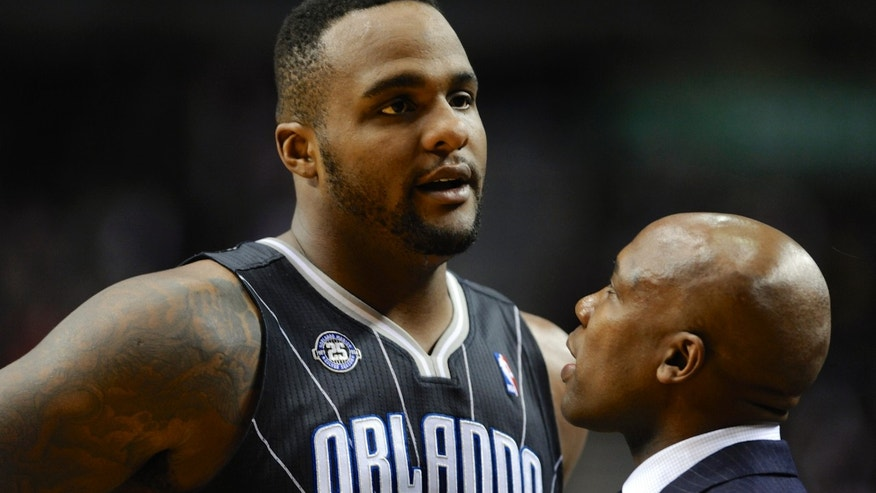 Orlando Magic coach Jacque Vaughn speaks with Glen Davis during a break in play against the Portland Trail Blazers during the first half of an NBA basketball game in Portland, Ore., Wednesday, Jan. 8, 2014. (AP Photo/Greg Wahl-Stephens)