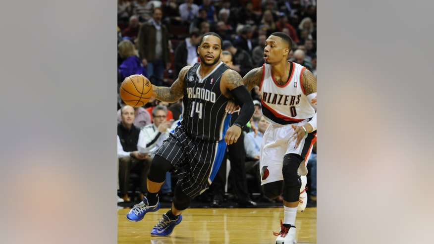 Orlando Magic's Jameer Nelson (14) drives against Portland Trail Blazers' Damian Lillard (0) during the first half of an NBA basketball game in Portland, Ore., Wednesday, Jan. 8, 2014. (AP Photo/Greg Wahl-Stephens)