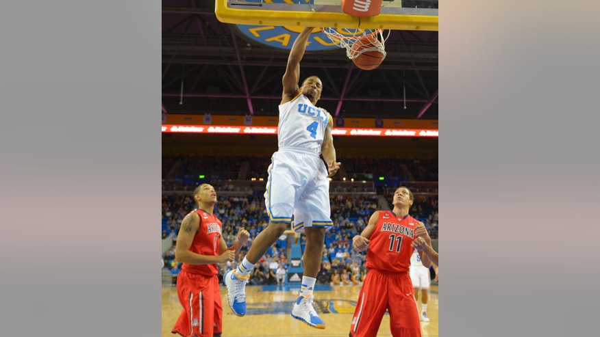 UCLA guard Norman Powell (4) dunks as Arizona forward Brandon Ashley, left, and forward Aaron Gordon defend during the first half of an NCAA college basketball game on Thursday, Jan. 9, 2014, in Los Angeles. (AP Photo/Mark J. Terrill)
