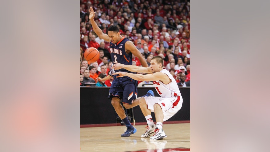 Wisconsin's Ben Brust, right, passes against Illinois' Joseph Bertrand during the second half of an NCAA college basketball game Wednesday, Jan. 8, 2014, in Madison, Wis. Wisconsin won 95-70. (AP Photo/Andy Manis)