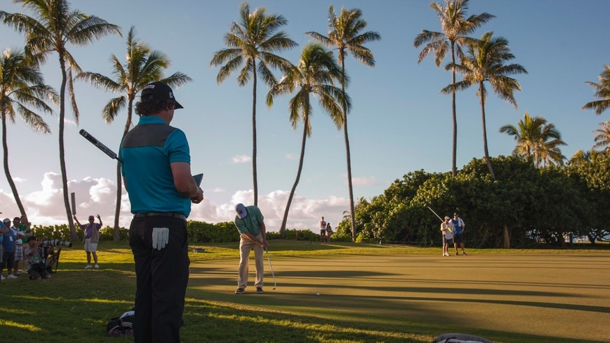 As Jason Dufner, left, watches, Matt Kuchar putts on the 11th green during the first round of the Sony Open golf tournament, Thursday, Jan. 9, 2014, in Honolulu. (AP Photo/Marco Garcia)