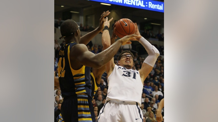 Xavier's Isaiah Philmore pulls a rebound down past Marquette's Chris Otule in the first half of their NCAA college basketball game at Xavier in Cincinnati, Thursday, Jan. 9, 2014. (AP Photo/Tom Uhlman)