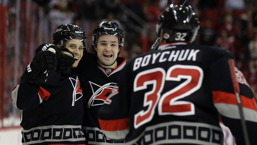 Carolina Hurricanes' John-Michael Liles, left, Ryan Murphy (7) and Zach Boychuk (32), celebrate Liles' goal against the Toronto Maple Leafs during the second period of an NHL hockey game in Raleigh, N.C., Thursday, Jan. 9, 2014. Carolina won 6-1. (AP Photo/Gerry Broome)