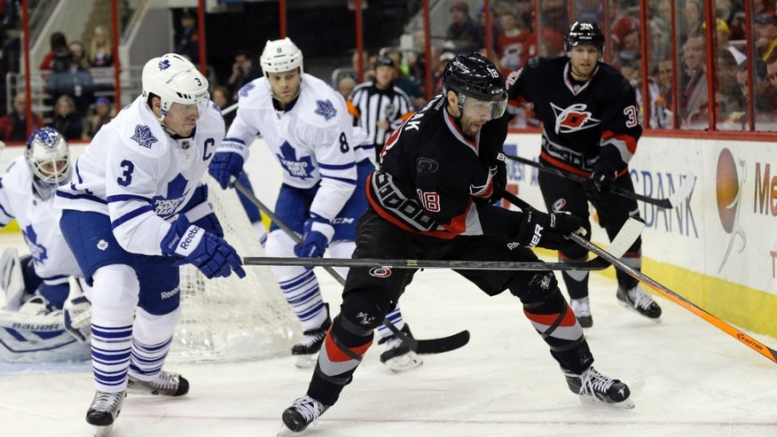 Carolina Hurricanes' Radek Dvorak (18), of the Czech Republic, chases the puck with Toronto Maple Leafs' Dion Phaneuf (3) and Tim Gleason (8) during the second period of an NHL hockey game in Raleigh, N.C., Thursday, Jan. 9, 2014. (AP Photo/Gerry Broome)