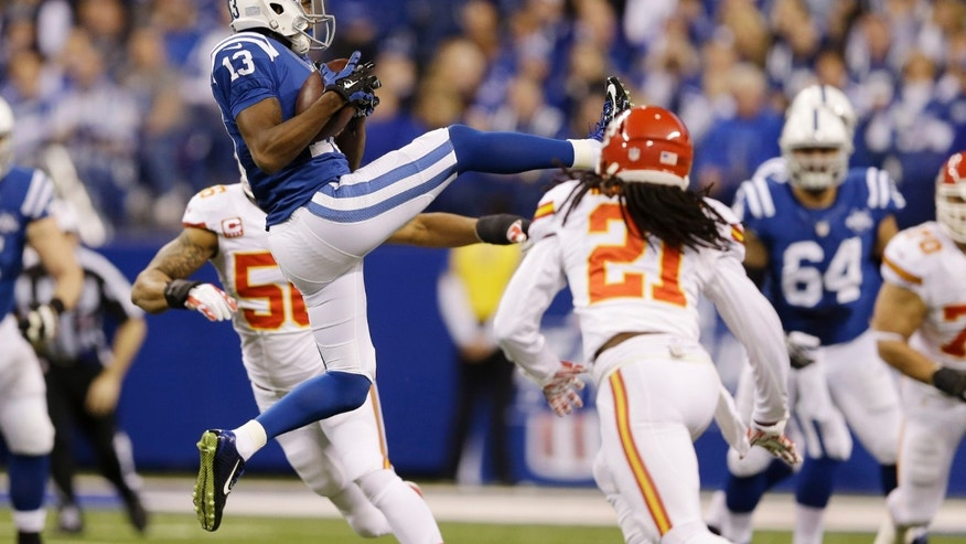 ADVANCE FOR WEEKEND OF JAN. 11-12 - FILE - In this Jan. 4, 2014, file photo, Indianapolis Colts wide receiver T.Y. Hilton (13) makes a catch as Kansas City Chiefs cornerback Dunta Robinson (21) moves in to defend during the first half of an NFL wild-card playoff football game in Indianapolis. After catching 24 passes for 379 yards over the past two weeks for the Colts, defenses are starting to take note of Hilton. (AP Photo/Michael Conroy, File)