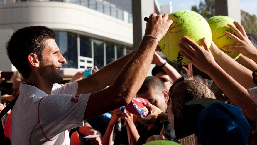 Serbia's Novak Djokovic signs autographs for fans following his exhibition match against Juan Monaco of Argentina at the Kooyong Classic ahead of the Australian Open tennis championship in Melbourne Australia, Thursday, Jan. 9, 2014. (AP Photo/Joshua Baker)