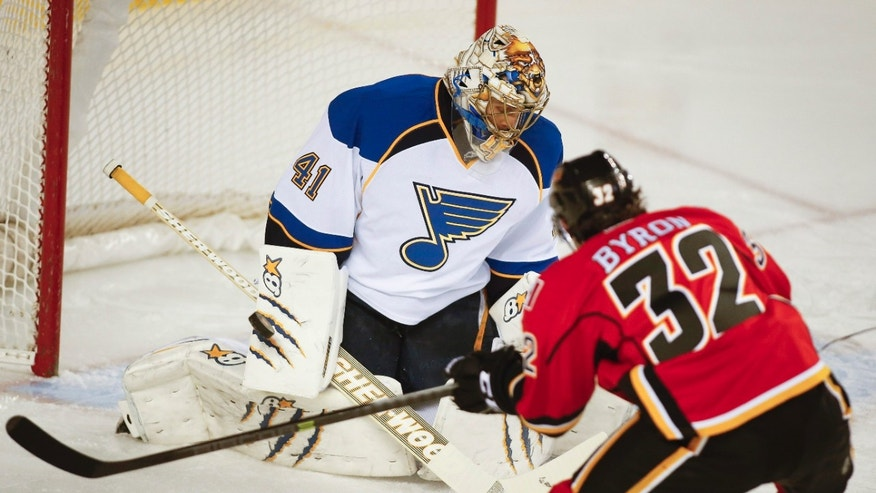 St. Louis Blues goalie Jaroslav Halak, left, from Slovakia, blocks a shot from Calgary Flames' Paul Byron during first-period NHL hockey game action against the Calgary Flames in Calgary, Alberta, Thursday, Jan. 9, 2014. (AP Photo/The Canadian Press, Jeff McIntosh)