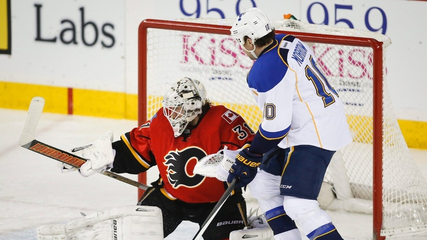 Calgary Flames goalie Karri Ramo, left, of Finland, makes a stop as St. Louis Blues' Brenden Morrow, right, looks for the rebound during first-period NHL hockey game action against the Calgary Flames in Calgary, Alberta, Thursday, Jan. 9, 2014. (AP Photo/The Canadian Press, Jeff McIntosh)