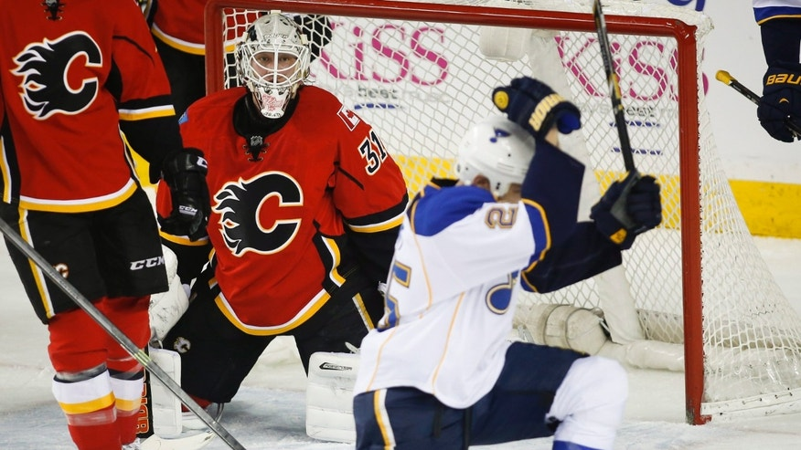 St. Louis Blues' Chris Stewart, right, celebrates his goal as Calgary Flames goalie Karri Ramo, from Finland, looks on during first-period NHL hockey game action against the Calgary Flames in Calgary, Alberta, Thursday, Jan. 9, 2014. (AP Photo/The Canadian Press, Jeff McIntosh)