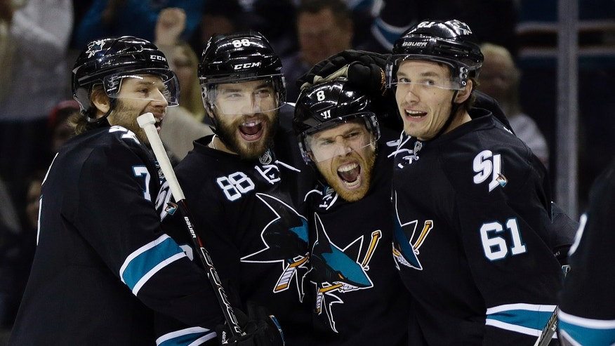 San Jose Sharks' Joe Pavelski (8) celebrates his goal with teammates Brad Stuart (7), Brent Burns (88) and Justin Braun (61) during the first period of an NHL hockey game against the Detroit Red Wings on Thursday, Jan. 9, 2014, in San Jose, Calif. (AP Photo/Marcio Jose Sanchez)