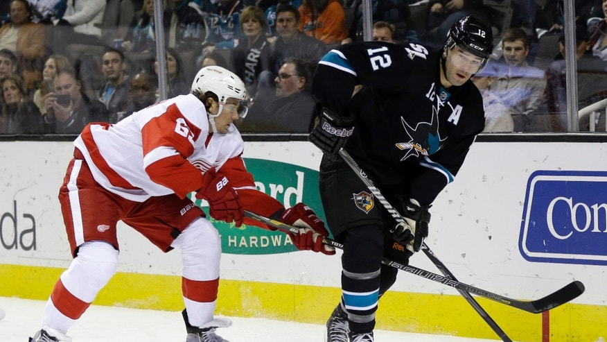 San Jose Sharks' Patrick Marleau (12) works with the puck against Detroit Red Wings' Danny DeKeyser (65) during the first period of an NHL hockey game on Thursday, Jan. 9, 2014, in San Jose, Calif. (AP Photo/Marcio Jose Sanchez)