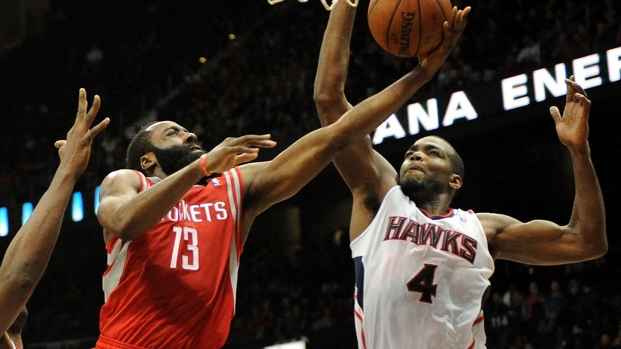 Atlanta Hawks' Paul Millsap (4) blocks the attempted basket by Houston Rockets' James Harden (13), who led the Rockets with 25 points, in the second half of an NBA basketball game on Friday, Jan. 10, 2014, in Atlanta. Atlanta won 83-80. (AP Photo/David Tulis)