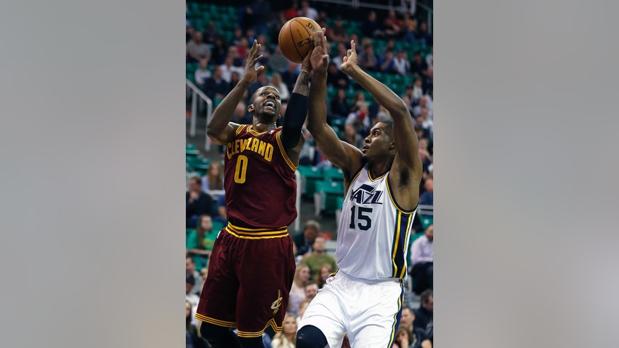 Cleveland Cavaliers C.J. Miles, left, shoots the ball past Utah Jazz's Derrick Favors during the first half of an NBA basketball game in Salt Lake City, Friday, Jan. 10, 2014. (AP photo/George Frey)