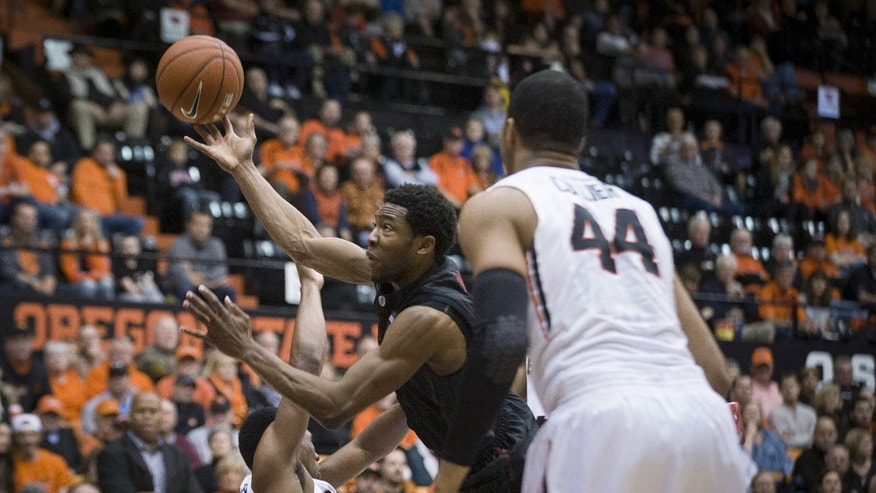 Stanford guard Chasson Randle, center, drives past Oregon State's Langston Morris-Walker, left and Devon Collier, right during the first half of an NCAA college basketball game in Corvallis, Ore., Thursday, Jan. 9, 2014.  (AP Photo/Karl Maasdam)