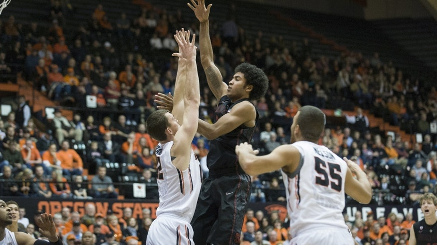 Stanford's Josh Huestis, center, shoots over Oregon State's Angus Brandt, left and Roberto Nelson right, during the first half of an NCAA college basketball game in Corvallis, Ore., Thursday, Jan. 9, 2014. (AP Photo/Karl Maasdam)