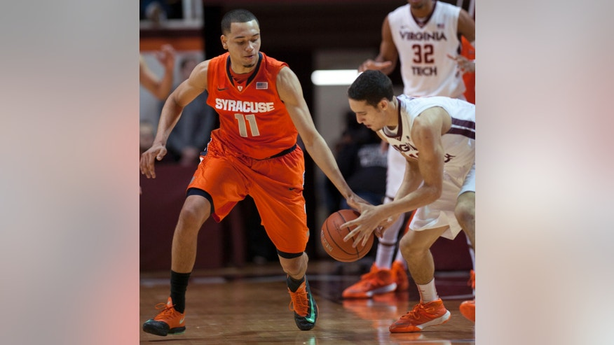 Syracuse's Tyler Ennis (11) goes for a steal against Virginia Tech's Devin Wilson during the second half of an NCAA college basketball game Tuesday, Jan. 7,  2014, in Blacksburg, Va. Syracuse won 72-52. (AP Photo/Don Petersen)