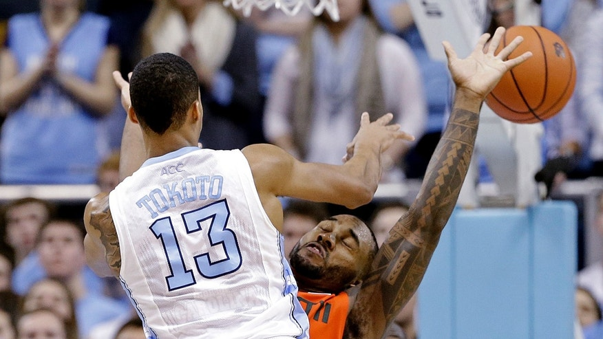 North Carolina's J.P. Tokoto (13) passes as Miami's Erik Swoope defends during the second half of an NCAA college basketball game in Chapel Hill, N.C., Wednesday, Jan. 8, 2014. Miami won 63-57. (AP Photo/Gerry Broome)