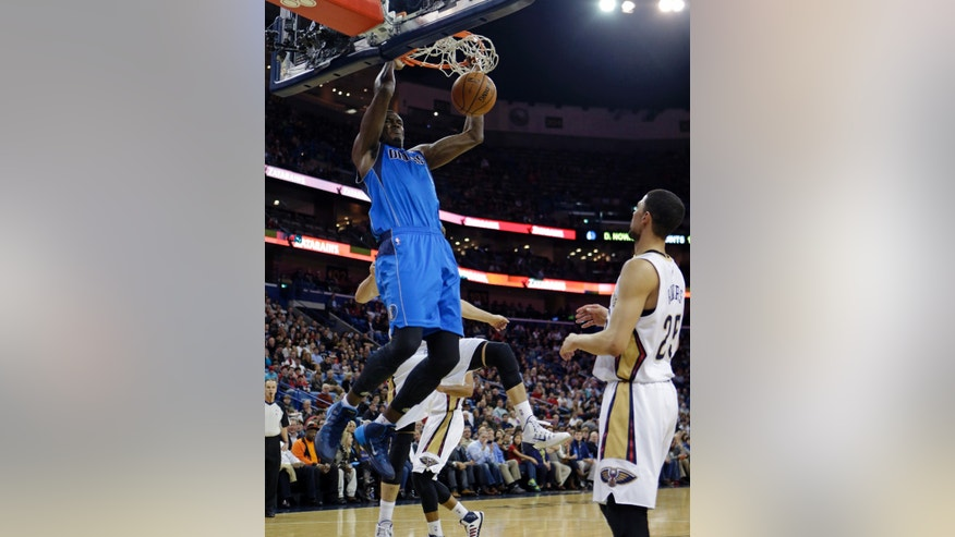Dallas Mavericks center Samuel Dalembert (1) slam-dunks in front of New Orleans Pelicans shooting guard Austin Rivers (25) in the first half of an NBA basketball game in New Orleans, Friday, Jan. 10, 2014. (AP Photo/Gerald Herbert)