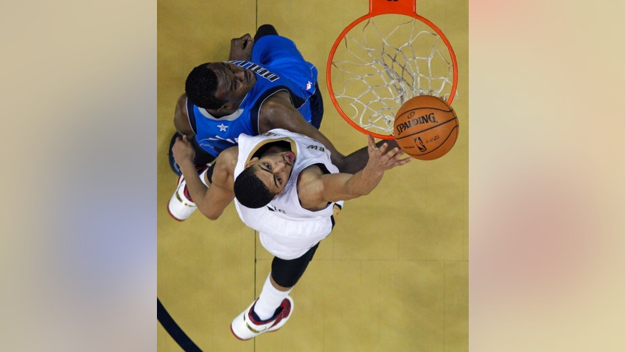 New Orleans Pelicans power forward Anthony Davis, bottom, shoots over Dallas Mavericks center Samuel Dalembert, top, in the first half of an NBA basketball game in New Orleans, Friday, Jan. 10, 2014. (AP Photo/Gerald Herbert)
