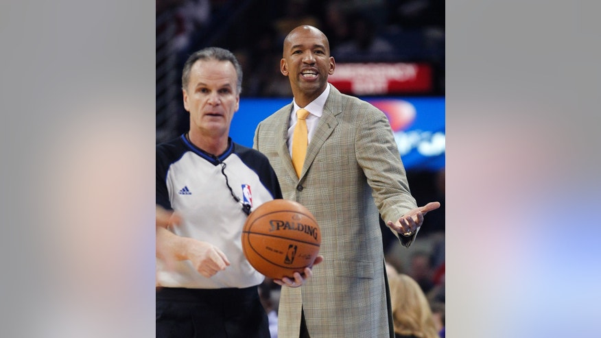 New Orleans Pelicans head coach Monty Williams, right, complains to an official who called a turnover in the first half of an NBA basketball game against the Dallas Mavericks in New Orleans, Friday, Jan. 10, 2014. (AP Photo/Gerald Herbert)