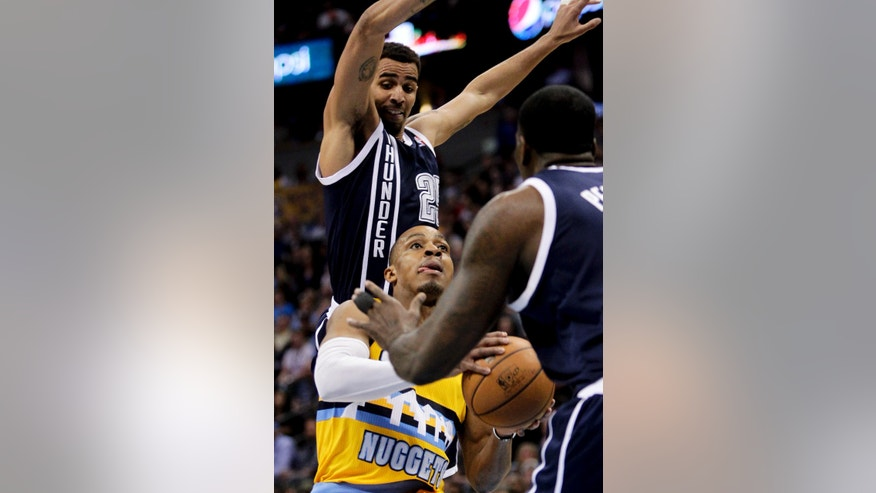 Oklahoma City Thunder's Thabo Sefolosha, top, leaps  behind Denver Nuggets' Randy Foye, bottom, during the first quarter of an NBA basketball game Thursday, Jan. 9, 2014, in Denver. (AP Photo/Barry Gutierrez)