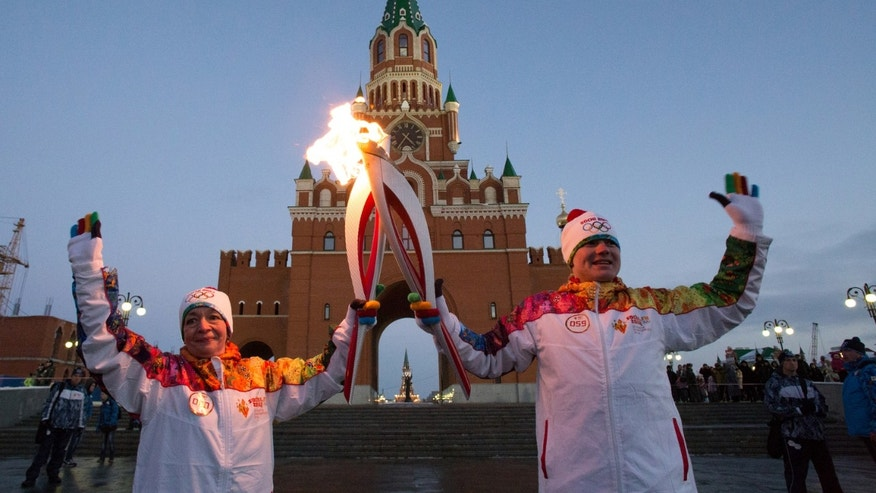 Dec. 28, 2013 - FILE photo of torch bearers, Marina Tartyshnaya, left, and Musa Galyamov during the Olympic torch relay in downtown Yoshkar-Ola, some 372 miles east of Moscow, Russia.