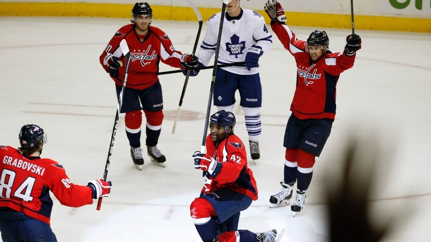 Washington Capitals right wing Joel Ward (42) celebrates his goal with center Mikhail Grabovski (84), center Marcus Johansson (90) and defenseman Mike Green (52), with Toronto Maple Leafs center Tyler Bozak (42) nearby, during the third period of an NHL hockey game, Friday, Jan. 10, 2014, in Washington. The Capitals won 3-2. (AP Photo/Alex Brandon)