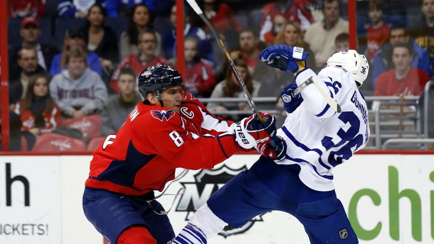 Washington Capitals right wing Alex Ovechkin (8), from Russia, collides with Toronto Maple Leafs defenseman Carl Gunnarsson (36), from Sweden, during the first period of an NHL hockey game, Friday, Jan. 10, 2014, in Washington. (AP Photo/Alex Brandon)
