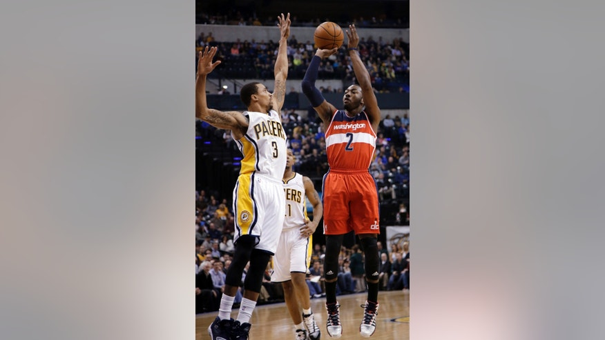 Washington Wizards guard John Wall, right, shoots over Indiana Pacers guard George Hill during the first half of an NBA basketball game in Indianapolis, Friday, Jan. 10, 2014. (AP Photo/AJ Mast)