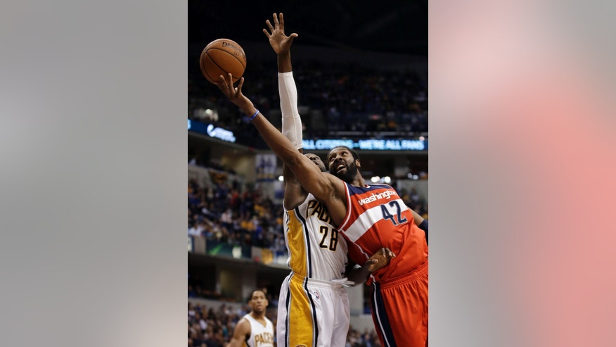 Washington Wizards forward Nene Hilario, right, of Brazil, shoots under the defense of Indiana Pacers center Ian Mahinmi during the first half of an NBA basketball game in Indianapolis, Friday, Jan. 10, 2014. (AP Photo/AJ Mast)