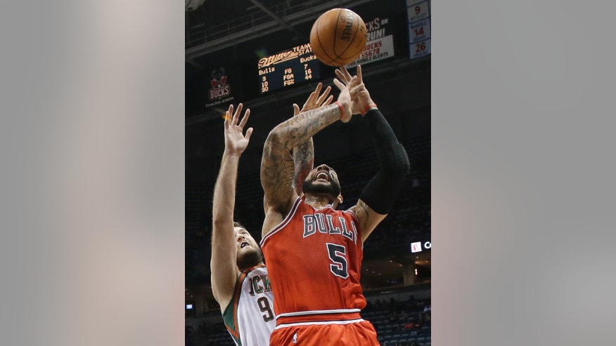 Chicago Bulls' Carlos Boozer is fouled by Milwaukee Bucks' Miroslav Raduljica (9) during the first half of an NBA basketball game Friday, Jan. 10, 2014, in Milwaukee. (AP Photo/Morry Gash)