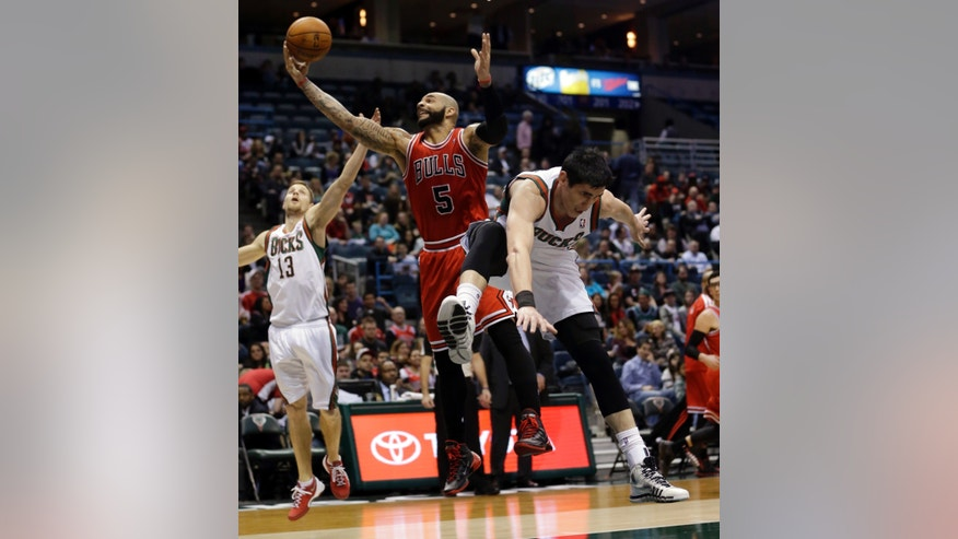 Chicago Bulls' Carlos Boozer (5) goes after a rebound between Milwaukee Bucks' Ersan Ilyasova and Luke Ridnour (13) during the first half of an NBA basketball game Friday, Jan. 10, 2014, in Milwaukee. (AP Photo/Morry Gash)