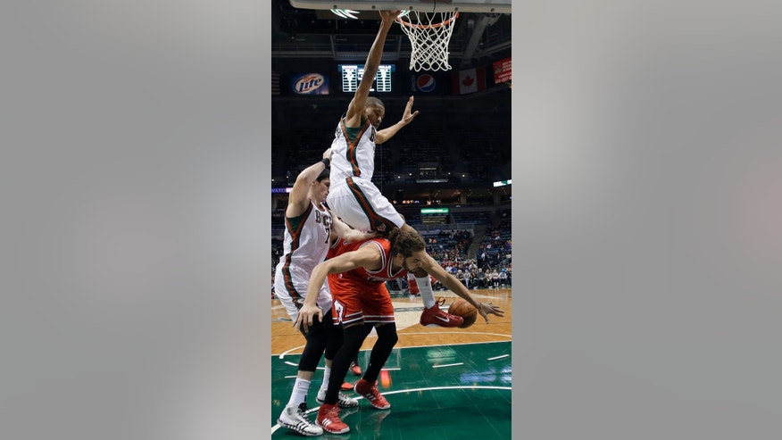 Milwaukee Bucks' Giannis Antetokounmpo fouls Chicago Bulls' Joakim Noah, bottom, as he lands on Noah during the first half of an NBA basketball game Friday, Jan. 10, 2014, in Milwaukee. (AP Photo/Morry Gash)