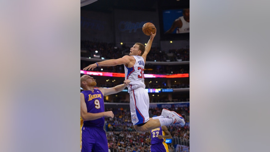 Los Angeles Clippers forward Blake Griffin, right, goes up for a dunk as Los Angeles Lakers center Chris Kaman defends during the first half of an NBA basketball game, Friday, Jan. 10, 2014, in Los Angeles. (AP Photo/Mark J. Terrill)