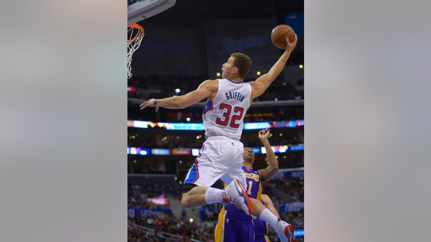 Los Angeles Clippers forward Blake Griffin goes up for a dunk as Los Angeles Lakers guard Wesley Johnson defends during the first half of an NBA basketball game, Friday, Jan. 10, 2014, in Los Angeles. (AP Photo/Mark J. Terrill)