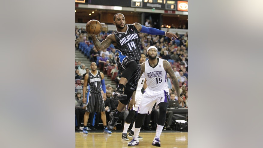 Orlando Magic guard Jameer Nelson, left, passes off as Sacramento Kings center DeMarcus Cousins, right, looks on during the first quarter of an NBA basketball game in Sacramento, Calif., Friday, Jan. 10, 2014. (AP Photo/Rich Pedroncelli)