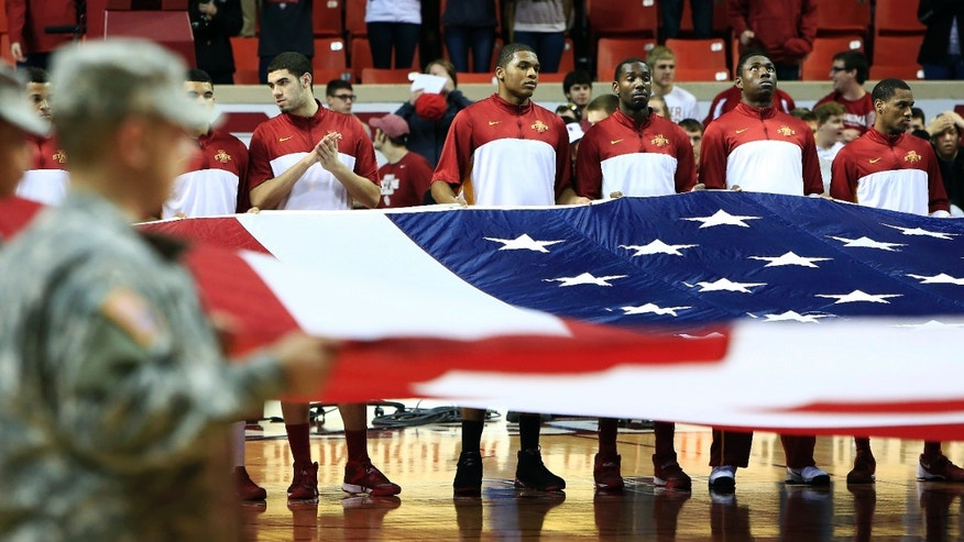 Iowa State members help hold the American flag before the start of an NCAA college basketball game against Oklahoma in Norman, Okla. on Saturday, Jan. 11, 2014. (AP Photo/Alonzo Adams)