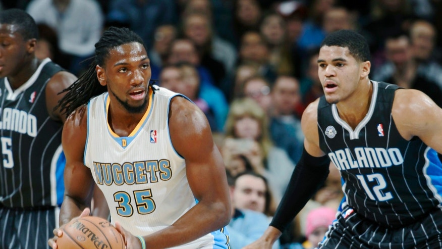 Denver Nuggets forward Kenneth Faried, left, looks to pass ball as Orlando Magic forward Tobias Harris covers in the first quarter of an NBA basketball game in Denver on Saturday, Jan. 11, 2014. (AP Photo/David Zalubowski)