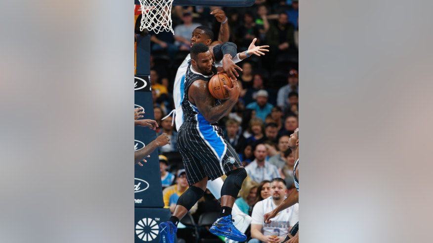 Orlando Magic center Glen Davis, front, pulls down rebound in front of Denver Nuggets forward Quincy Miller in the first quarter of an NBA basketball game in Denver on Saturday, Jan. 11, 2014. (AP Photo/David Zalubowski)