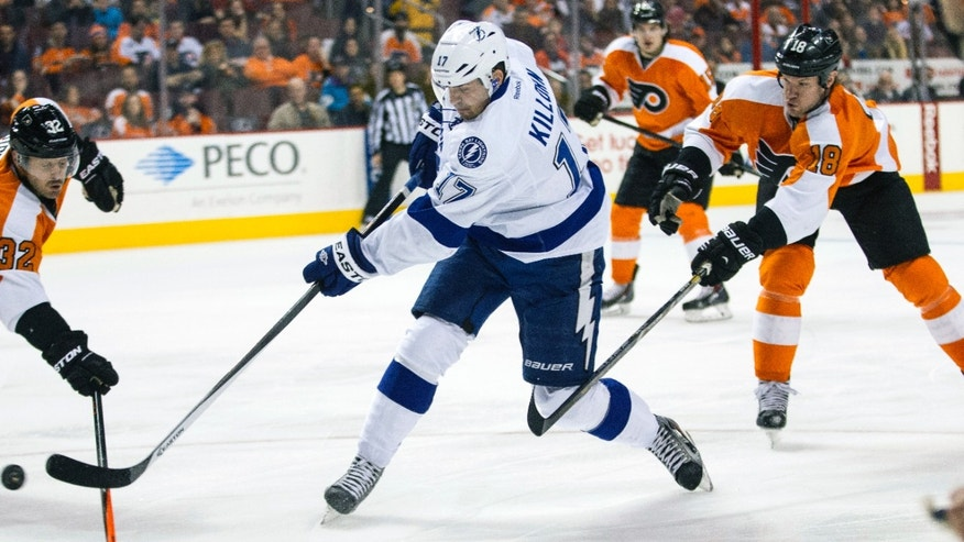 Tampa Bay Lightning's Alex Killorn, center, shoots the puck over the stick of Philadelphia Flyers' Mark Streit, left, of Switzerland, with Philadelphia Flyers' Adam Hall, right, reaching from behind with his stick during the first period of an NHL hockey game, Saturday, Jan. 11, 2014, in Philadelphia. (AP Photo/Chris Szagola)