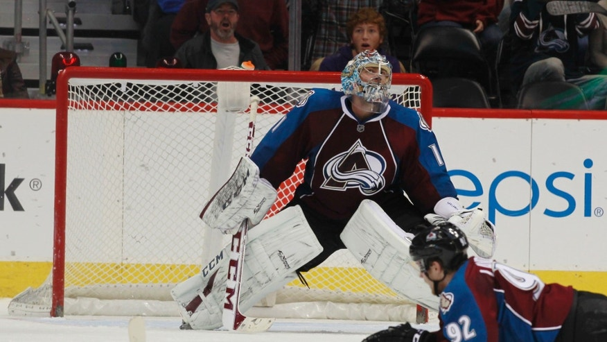 Colorado Avalanche goalie Semyon Varlamov, back, of Russia, reacts after giving up the winning goal to New York Islanders right wing Michael Grabner in overtime of the Islanders' 2-1 victory in an NHL hockey game in Denver on Friday, Jan. 10, 2014. Avalanche left wing Gabriel Landeskog is at front. (AP Photo/David Zalubowski)