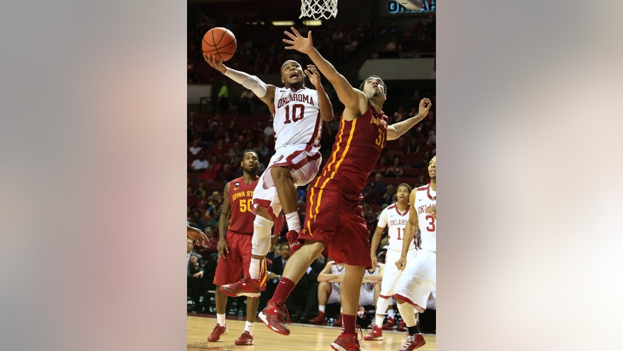 Oklahoma guard Jordan Woodard, left, goes to the basket as Iowa State guard Georges Niang, right, defends during the second half of an NCAA college basketball game in Norman, Okla., on Saturday, Jan. 11, 2014. Oklahoma won 87-82. (AP Photo/Alonzo Adams)