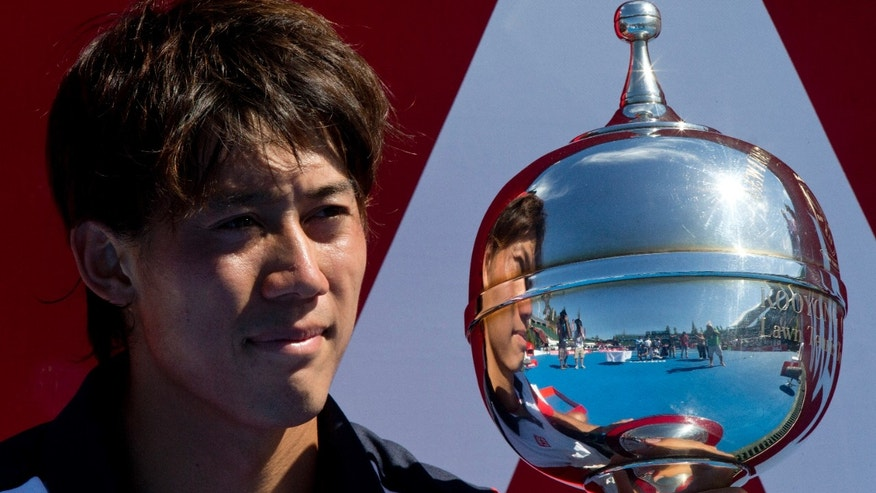 Japan's Kei Nishikori holds the trophy after win over Tomas Berdych of the Czech Republic in their final match of the Kooyong Classic ahead of the Australian Open tennis championship in Melbourne, Australia, Saturday, Jan. 11, 2014. (AP Photo/Joshua Baker)