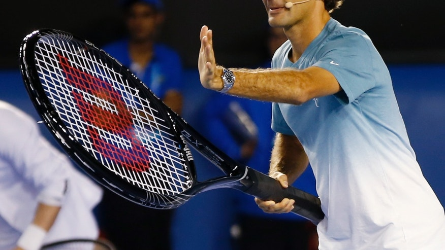 Switzerland's Roger Federer prepares to play a shot with a giant tennis racquet during an exhibition match on Kids Tennis Day ahead of the Australian Open tennis championship in Melbourne, Australia, Saturday, Jan. 11, 2014. (AP Photo/Eugene Hoshiko)