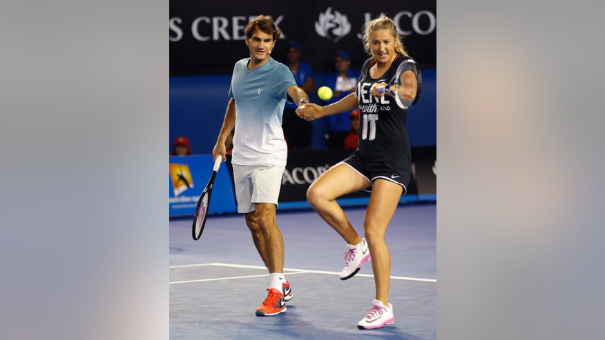Victoria Azarenka of Belarus plays a shot as she holds hands with Switzerland's Roger Federer during an exhibition match on Kids Tennis Day ahead of the Australian Open tennis championship in Melbourne, Australia, Saturday, Jan. 11, 2014. (AP Photo/Eugene Hoshiko)