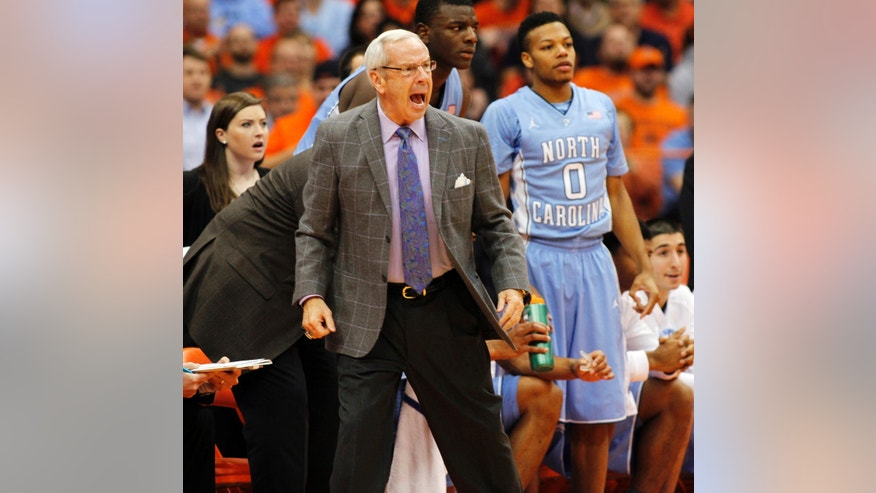North Carolina's head coach Roy Williams, center, yells to his players in the first half of an NCAA college basketball game against Syracuse in Syracuse, N.Y., Saturday, Jan. 11, 2014. (AP Photo/Nick Lisi)
